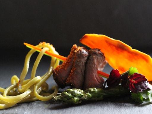 Groene theenoedels met biefstuk, aspergepunten, bataat en sesamdressing